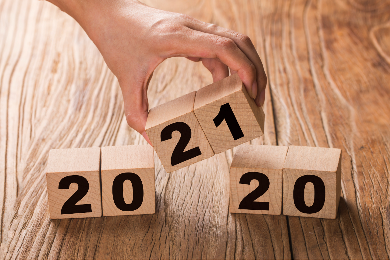 A hand holds building blocks that replace 2020 with 2021.