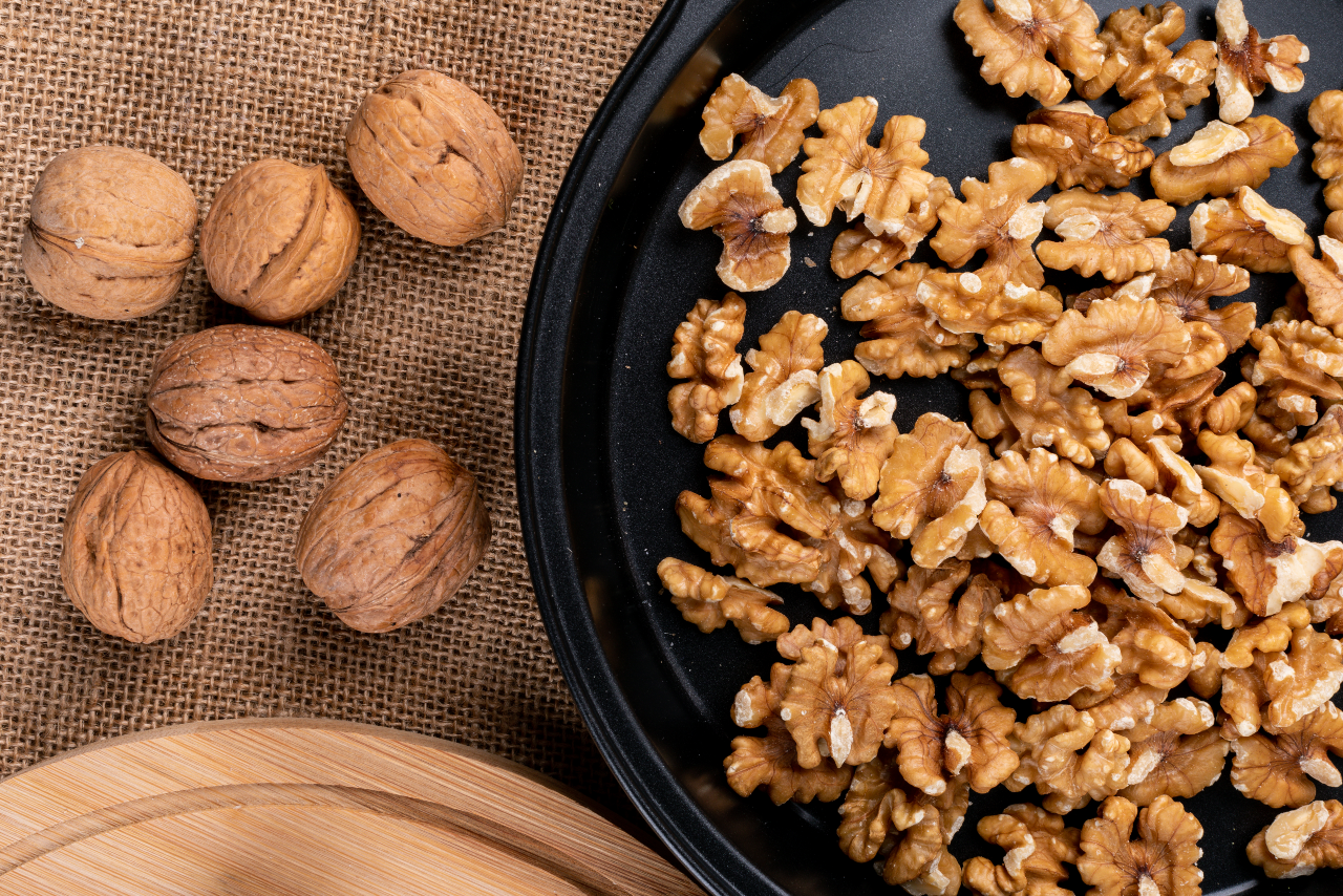 A bowl full of shelled walnuts sits alongside several shelled walnuts.