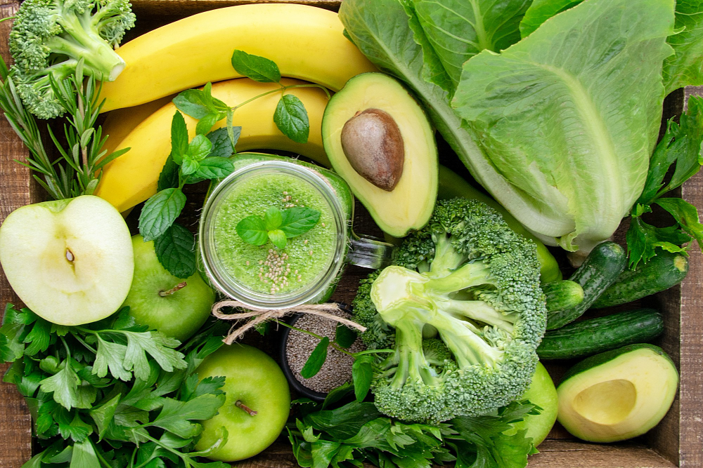 Raw Foods for Healthy Skin - picture shows a variety of healthy raw foods including bananas, broccoli, avocado, apples, romaine lettuce and a green smoothie