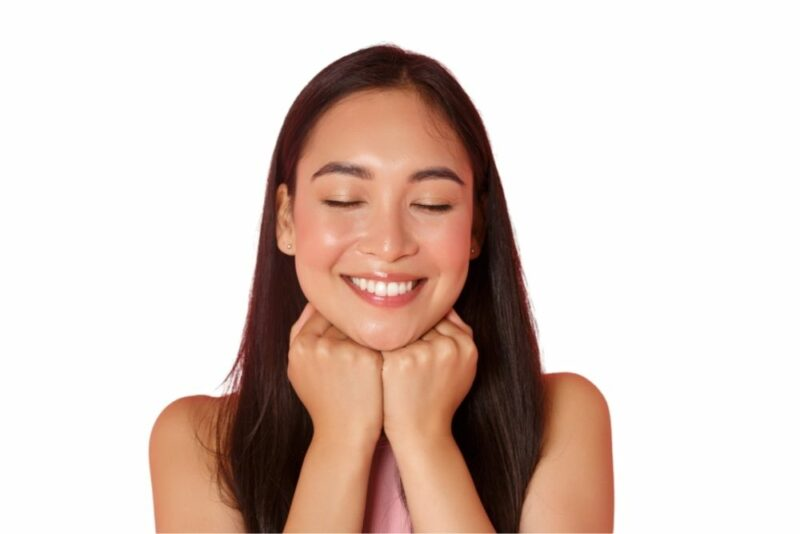 Probiotics, Gut Health & Glowing Skin - picture of a woman with eyes closed with a smile and radiant skin